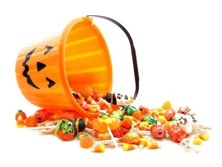 Halloween candy and jackolantern bucket. Image included in dental blog to explain how to protect your teeth during the holidays.